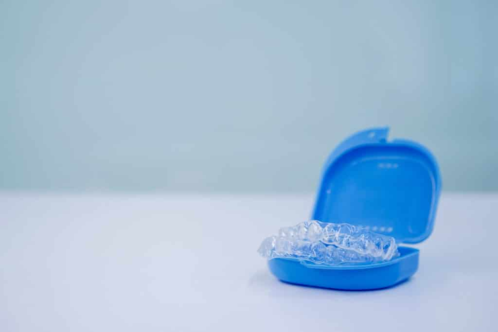 an image of clear aligners in a tray on an empty table
